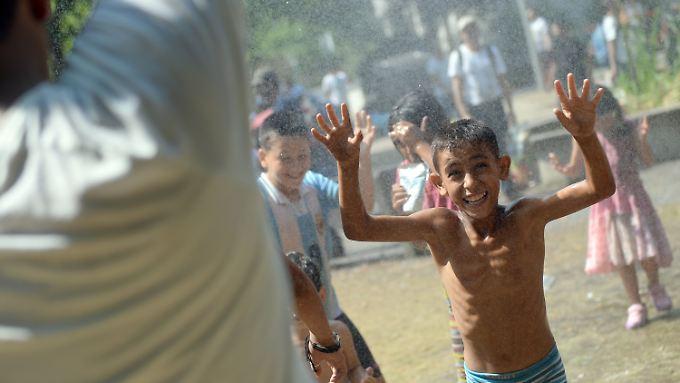 Am vergangenen Freitag vor dem Berliner Landesamt für Gesundheit und Soziales: Die Flüchtlinge mussten im Freien campieren, konnten sich aber immerhin abkühlen.