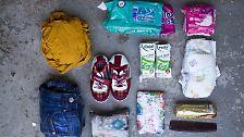 Sie enthält: Ein T-Shirt, eine Jeans, ein Paar Schuhe. Waschzeug, eine Windel, zwei kleine Tüten Milch und einige Kekse, persönliche Dokumente, Bargeld, Hygieneartikel und einen Kamm.