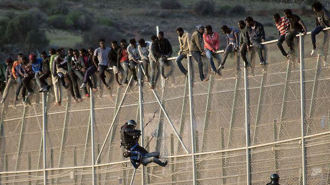Flüchtlinge auf dem Grenzzaun der spanischen Enklave Ceuta in Marokko.