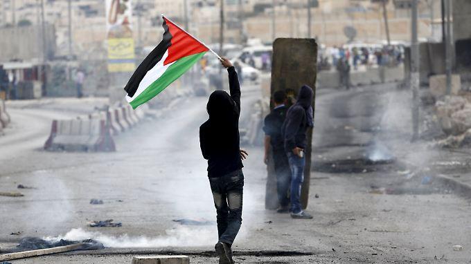 Ein palästinensischer Demonstrant hält seine Landesflagge hoch, während es mit der israelischen Arme zu Zusammenstößen kommt.