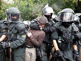 Aus dem Weg geräumt: Polizisten führen einen Demonstranten ab.