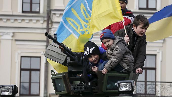 Ukrainische Kinder spielen in Kiew auf einem Panzer.