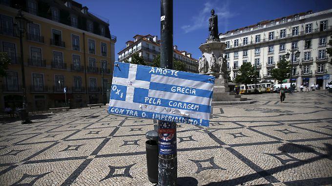 """Eine griechische Flagge im Sommer auf dem Praça Luís de Camões, ein zentraler Platz in der Innenstadt der portugiesischen Hauptstadt Lissabon. Auf der Flagge steht: """"Ich liebe dich, Griechenland. Für deinen Mut gegen Imperialismus!"""""""