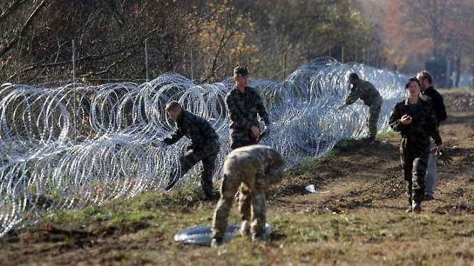 Slownische Soldaten errichten an der Grenze zu Kroatien eine Stacheldrahtbarriere.