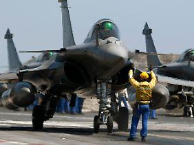 Gefährlicher Arbeitsplatz: Spezialisten an Deck weisen den Piloten in ihren waffenstarrenden Rafales die richtige Startposition zu.