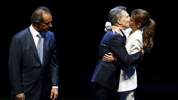 Juliana Awada küsst Mauricio Macri - Daniel Scioli schaut zu.