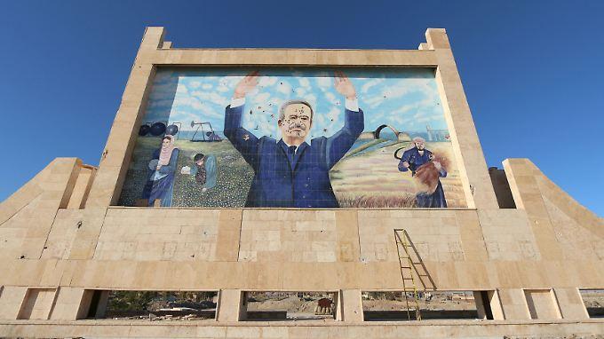 Lang ist's her: Noch immer grüßt Hafiz al-Assad, der vor 15 Jahren verstorbene Vater von Baschar al-Assad, in Syrien von Plakaten. Sein einst mit harter Hand regiertes Land gibt es nicht mehr.