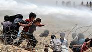 Kinder fliehen im Juni durch den Stacheldraht an der türkisch-syrischen Grenze vor den Gefechten kurdischer Kämpfer und dem IS. Der türkische Fotograf Bülent Kilic hat diese Tragödie für die französische Nachrichtenagentur AFP festgehalten.