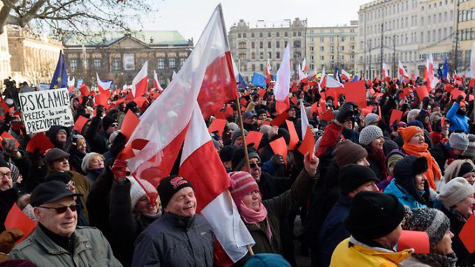Mit roten Karten demonstrieren viele Polen gegen das umstrittene Mediengesetz.