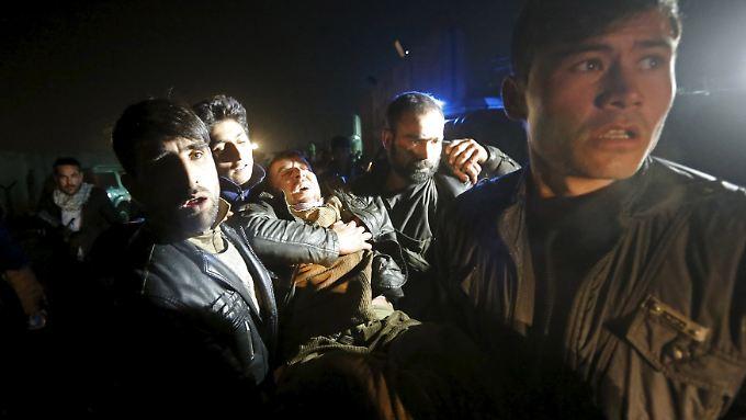 Nach einer Explosion in Kabul tragen Männer einen Verwundeten davon.