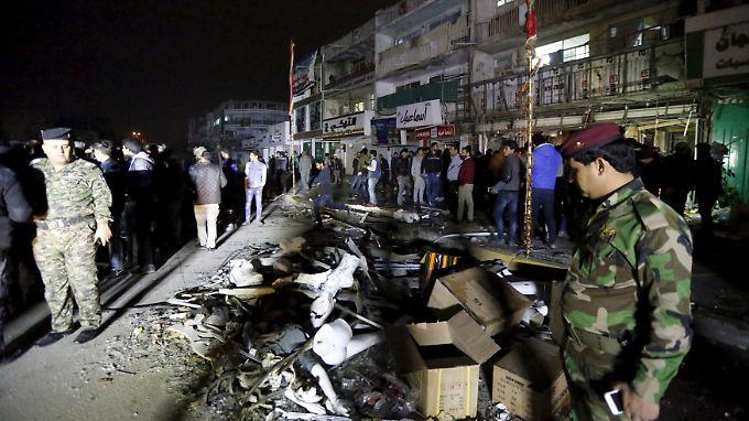Polizisten sichern die Straße in Bagdad, wo eine Autobombe explodierte.