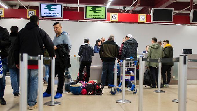 Reisende und Flüchtlinge stehen im Flughafen Tegel am Check-In-Schalter für einen Flug nach Erbil.