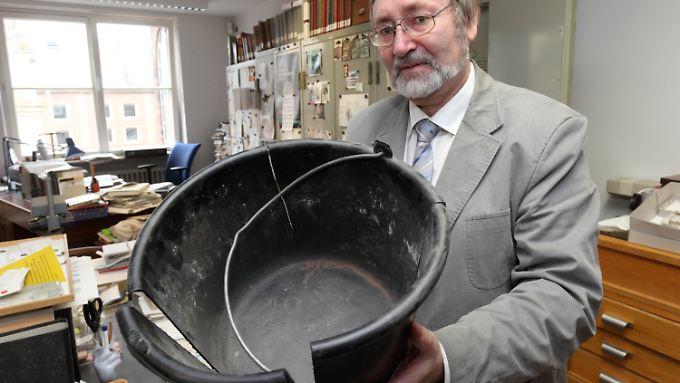 Der Numismatiker und Archäologe Karl-Josef Gilles mit dem Eimer, in dem 1993 der spektakuläre Fund römischer Goldmünzen angeliefert wurde.