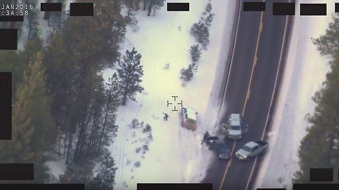 """Blutiges Ende im Konflikt mit der Staatsgewalt: Die Straßensperre aus der Luft, Robert """"LaVoy"""" Finicum steht mit erhobenen Armen links neben dem weißen Geländewagen."""