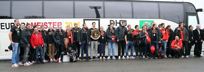 Die deutschen Handballer vor dem Fanbus in Berlin-Tegel.