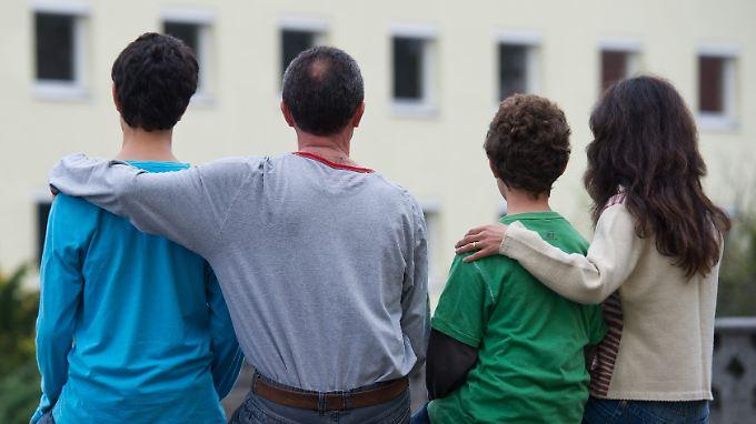 Eine syrische Familie sitzt vor einem Asylwohnheim der Zentralen Ausländerbehörde des Landes Brandenburg.