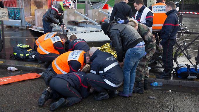 Erste Hilfe am Unfallort: Rettungskräfte bemühen sich in Paris um die beiden Schwerverletzen.