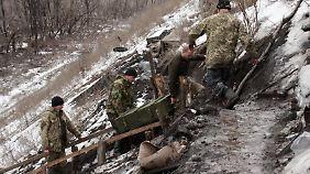 Ukrainische Soldaten verlegen eine Munitionskiste zu ihrem Stützpunkt in der Nähe von Donezk.