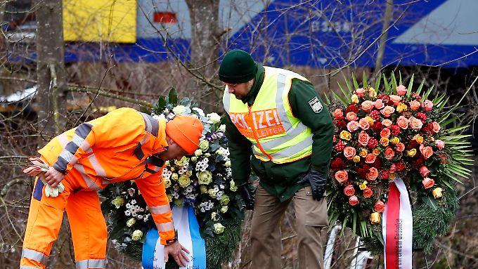Vertreter der Einsatzkräfte arrangieren einen Kranz für die Opfer des Zugunfalls von Bad Aibling.