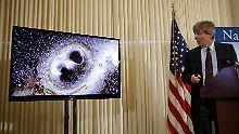 Dieses Ereignis soll Schockwellen durch Raum und Zeit ausgesandt haben: Einer der Ligo-Wissenschaftler führt auf der Bühne den Zusammenstoß zweier Schwarzer Löcher in der Videografik vor.