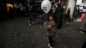 """Ein Mädchen in Damaskus trägt eine Ballon mit der Aufschrift """"I love you"""" durch den al-Hamidiyah Markt."""