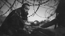 Ein Vater reicht sein Baby durch den Stacheldraht am Grenzzaun von Ungarn. Der australische Fotograf Warren Richardson hält die Szene im Bild fest - und macht das Welt-Presse-Foto des Jahres 2015.