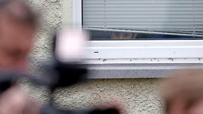 Ein Flüchtlingsjunge beobachtet Journalisten vor der Flüchtlingsunterkunft in Clausnitz.