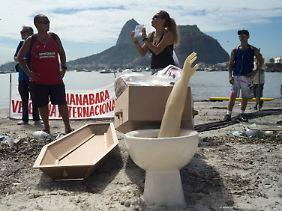 Umweltaktivisten beerdigen am Botafogo-Beach die verdreckte Bucht symbolisch - mit einer Toilettenschüssel, einem amputierten Arm aus Plastik sowie weiterem Müll.