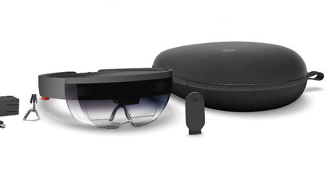 """Die HoloLens wird mit Ladeteil, Extra-Nasenbügel, Transporttasche und """"Clicker"""" ausgeliefert. Das kleine Accessoir dient in Interaktionen zum Auswählen, Scrollen oder Stoppen."""