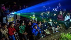 Ein wenig Ablenkung: Flüchtlingskinder schauen mit einem Beamer Cartoons - das Bild wird auf die Seite eiens Lieferwagens projeziert.
