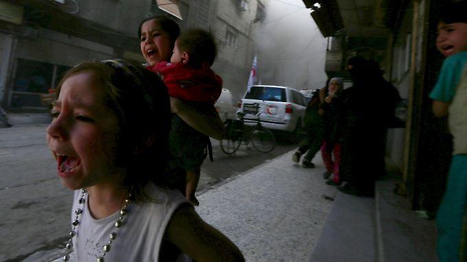 Kinder fliehen vor den Explosionen eines Luftangriffs in einem Vorort von Damaskus.
