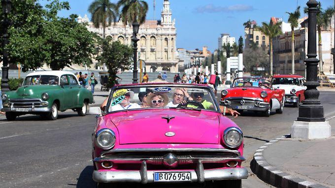 Klassiker: Touristen fahren in einem Oldtimer durch Havanna.