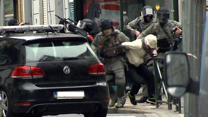 Schwer bewaffnete Einsatzkräfte überwältigen einen Verdächtigen - ob es sich um Abdeslam handelt, ist unklar (Standbild des belgischen TV-Senders VTM).