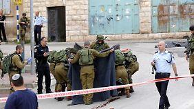 Israelische Soldaten verhüllen die Leiche des Attentäters mit einer Decke.
