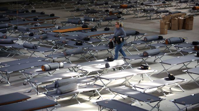 Eine Helferin verteilt in einer Erstaufnahmestelle bei Hamburg Feldbetten, Campingmatratzen und Schlafsäcke.