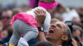 Obama posiert mit einem Baby.