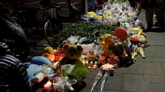 Zahlreich Menschen bringen Blumen und Kuscheltiere an den Ort des Geschehens.