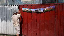 Ein Straßenverkäufer hängt Bilder der Aktopolis an einen Bauzaun in der Altstadt von Athen.
