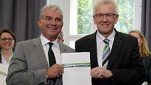 Kretschmann (r.) und Strobl präsentieren das Vertragswerk, das ein Novum in der bundesdeutschen Geschichte darstellt.