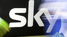 Spieler gehen vor dem Spiel an einer Sky-Werbefläche vorbei. Foto: Arne Dedert