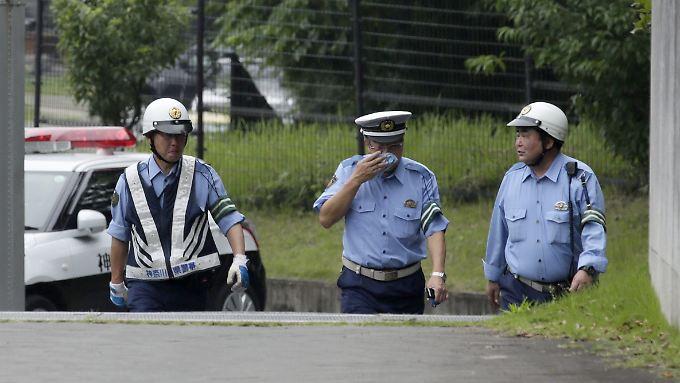 Ein Polizist wischt sich nach einer Besichtigung des Tatorts Tränen aus den Augen.