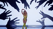 In einem glitzernden gelben Einteiler mit Cut-Outs an den Seiten und einem tiefen Ausschnitt räkelt sie sich lasziv auf der Bühne.
