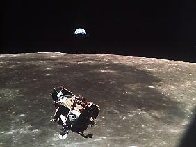 Die Rückkehrstufe der Mondfähre mit den Astronauten Neil Armstrong und Edwin Aldrin an Bord schwebt am 20. Juli 1969 über dem Mond kurz vor dem Ankoppeln an die Apollo-Kapsel, im Hintergrund die Erde.