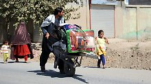 Mit gepackter Sackkarre verlässt eine Familie die Stadt, um den Kämpfen zwischen Taliban und afghanischen Sicherheitskräften zu entkommen.