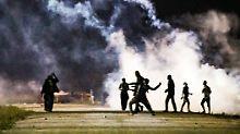 Randale in Calais: Flüchtlinge werfen Steine, die Polizei setzt Tränengas ein.