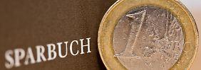 Ein-Euro-Münze liegt neben Sparbuch