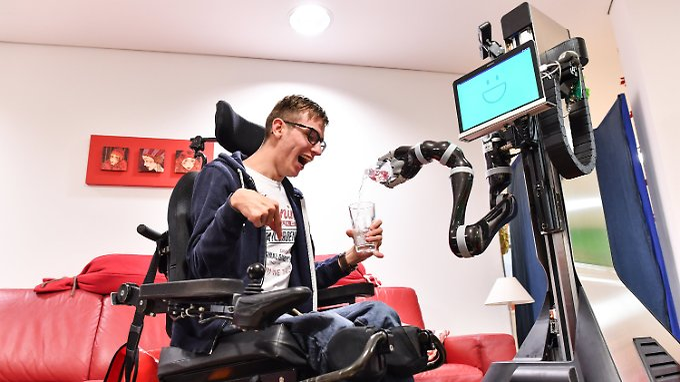 Roboter Marvin schenkt Rollstuhlfahrer Marvin Thurner ein Glas Wasser ein.