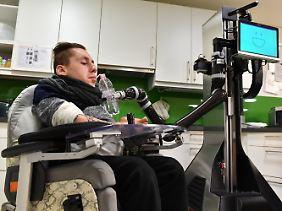 Sascha Dohrn bedient mit einer Mundsteuerung Roboter Marvin, der ihm eine Flasche Wasser reichen soll.