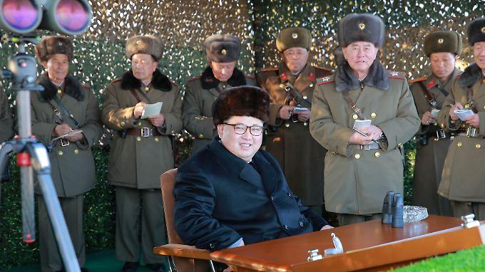 Nordkoreas Machthaber Kim Jong Un schaut sich in Gegenwart seiner Generäle kurz vor Weihnachten einen Test von Raketenwerfern an.