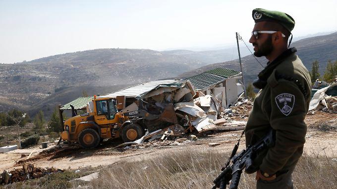 Ein israelischer Polizist beobachtet, wie ein Haus auf annektiertem israelischen Gebiet bei Amona zerstört wird.